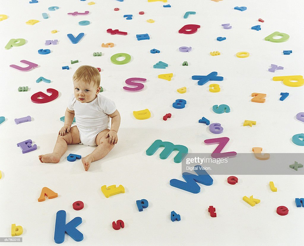 Portrait of a Toddler Sitting Amongst a Large Group of Letters of the Alphabet : Stock Photo