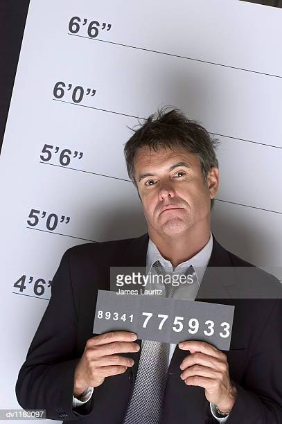 Portrait of a Tough Criminal Businessman Holding an Identity Card in a Police Line Up