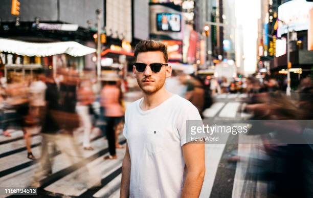 portrait of a tourist wearing sunglasses in a bustling city street in new york - bewegungsunschärfe stock-fotos und bilder