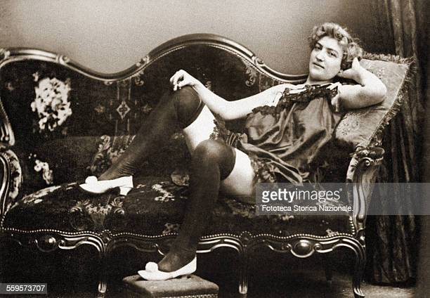 Portrait of a transgender woman lying in seductive pose on the sofa, dressed with only underwear. Italy approx. 1900 .