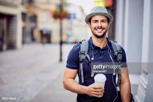 Portrait of a traveler with backpack holding coffee