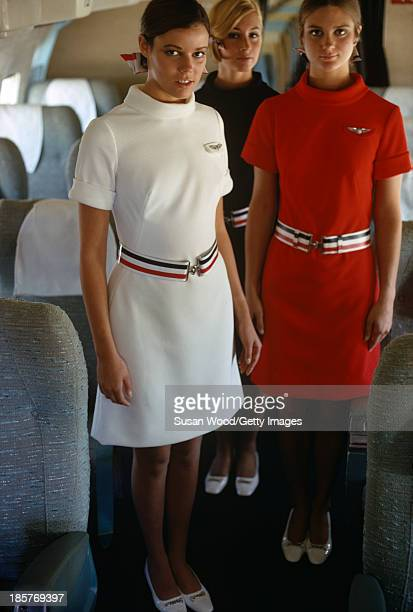 Portrait of a trio of American Airlines air stewardesses as they pose in uniform in the aisle of an airplane September 1967 The photo was taken as...