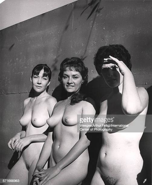 Portrait of a trio of female nudists as they lean against a wall in the sun twentieth century Photo by Weegee /International Center of...