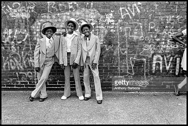 Portrait of a trio of smiling welldressed young boys as they pose on a Harlem street New York New York 1975