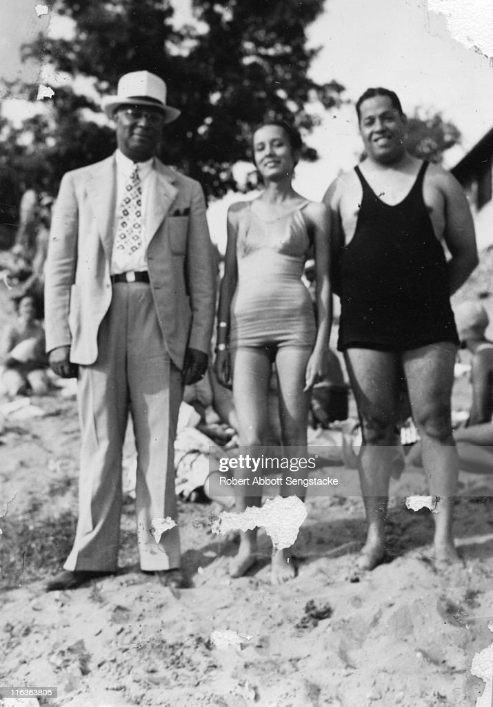 Portrait of a trio of unidentified people (friends and/or family members of future newspaper publisher John H. Sengstacke) as they pose on the beach, Idlewild, Michigan, September 1938. Idlewild, known as 'the Black Eden,' was a resort community that catered to African Americans, who were excluded from other resorts prior to the passage of the Civil RIghts Act of 1964.