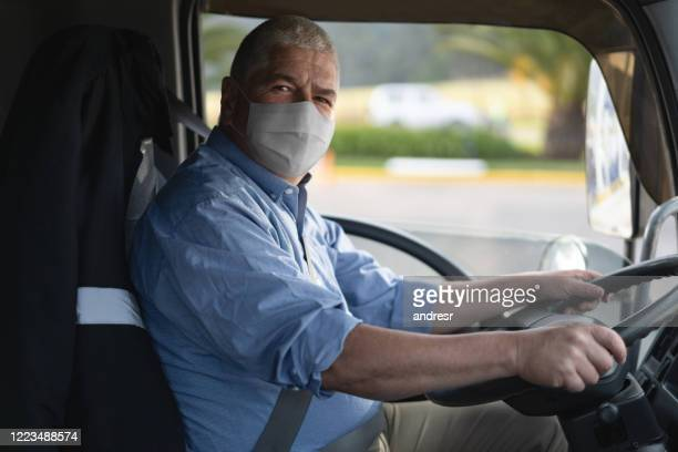 portrait of a truck driver wearing a facemask to avoid the coronavirus - essential workers stock pictures, royalty-free photos & images