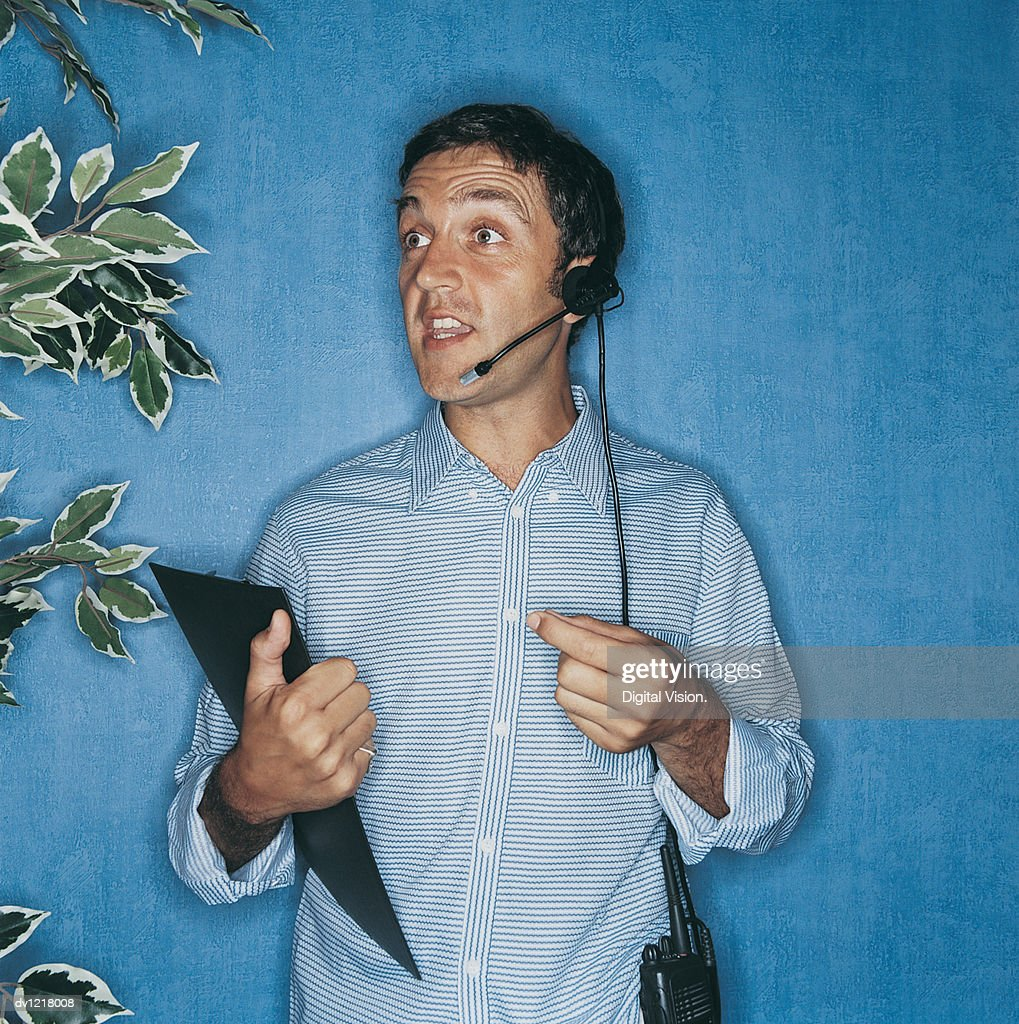 Portrait of a TV Producer Holding a Clipboard and Wearing a Headset in a TV Studio : Stock Photo