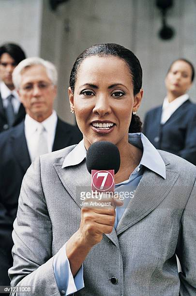 Portrait of a TV Reporter Talking Into a Microphone