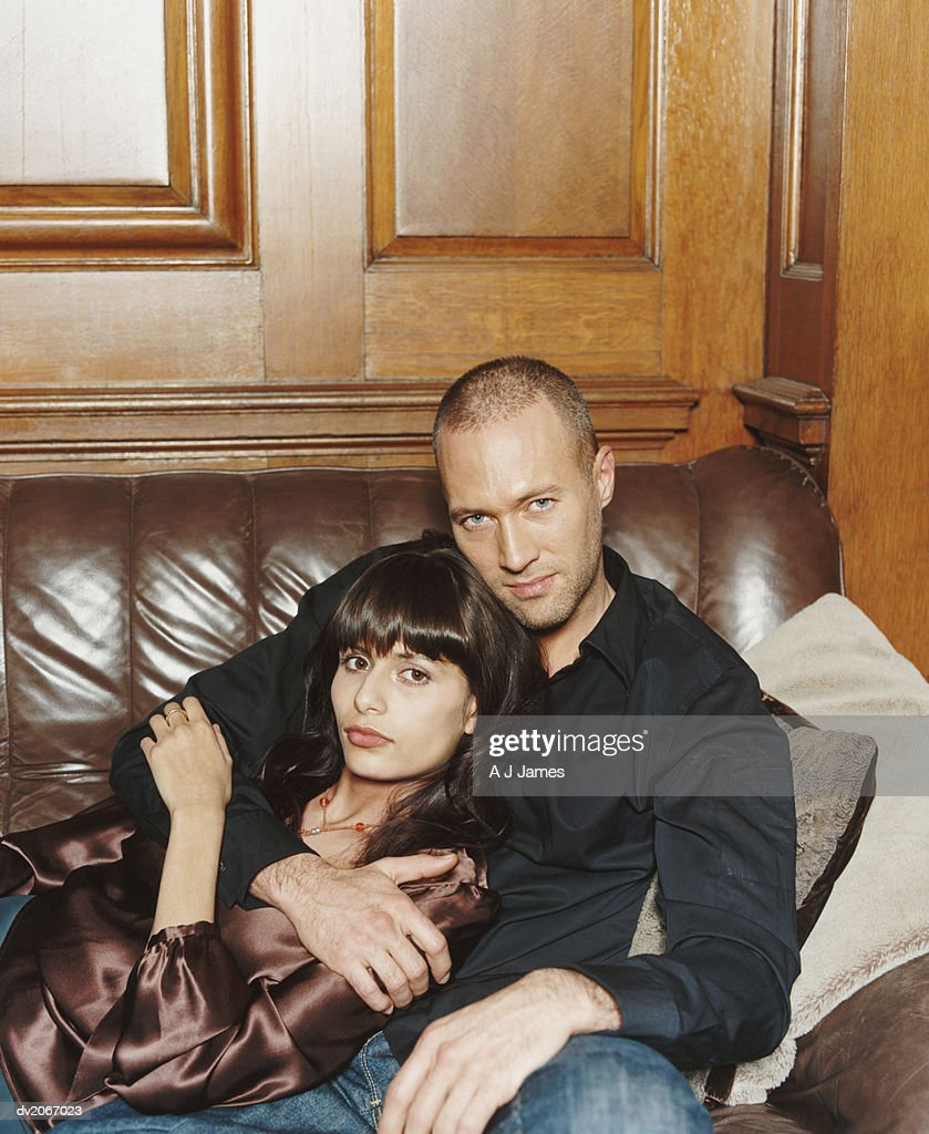 Portrait of a Twentysomething Couple Sitting on a Leather Sofa : Stock Photo