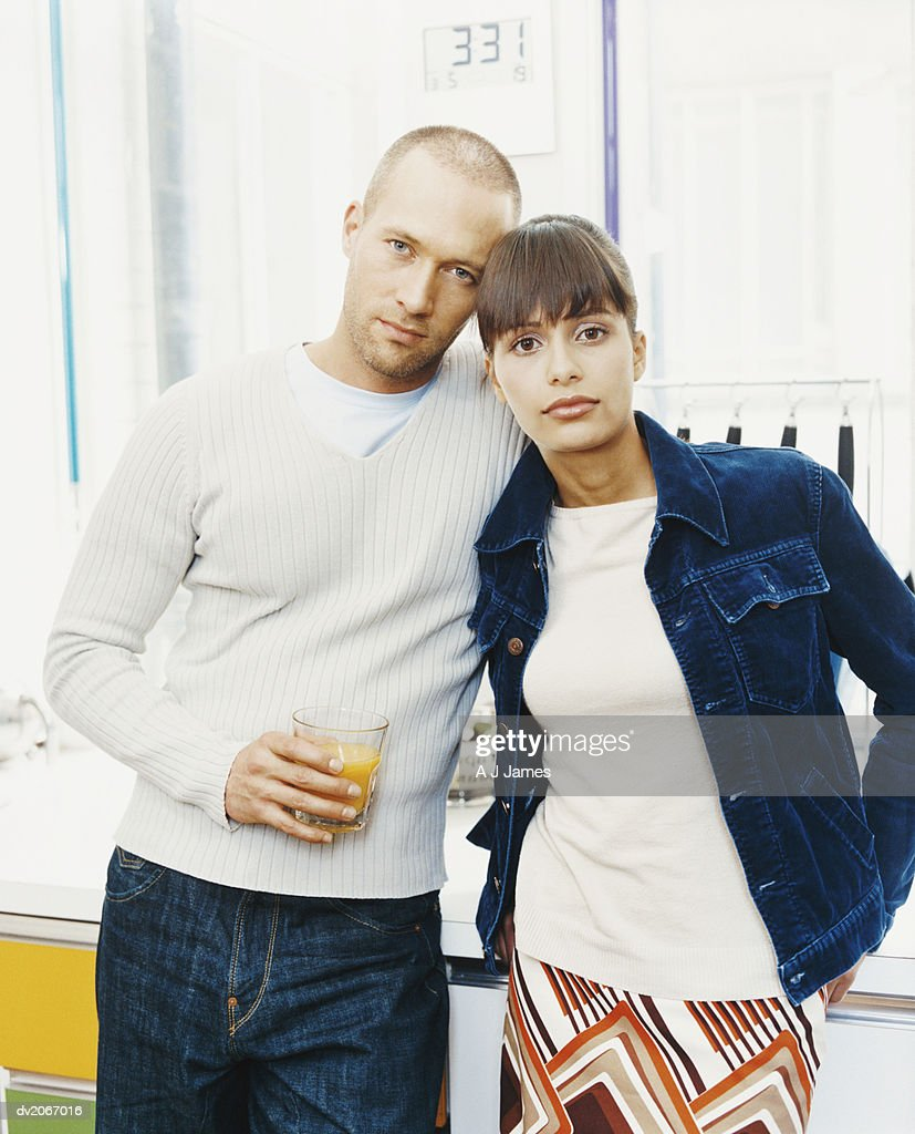 Portrait of a Twentysomething Couple, with the Man Holding a Glass of Orange Juice : Stock Photo