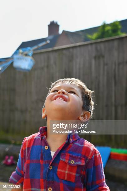 Portrait of a two year old boy laughing whilst looking up at the sky. 08baae2f04057