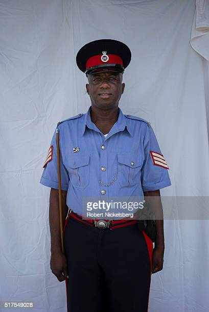 Portrait of a uniformed police officer as he stands before a white backdrop Hillsborough Carriacou island Grenada March 2 2016