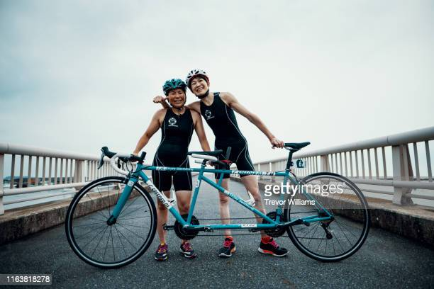 portrait of a visually impaired female triathlete and her guide and coach with their tandem bicycle - tandem bicycle stock pictures, royalty-free photos & images