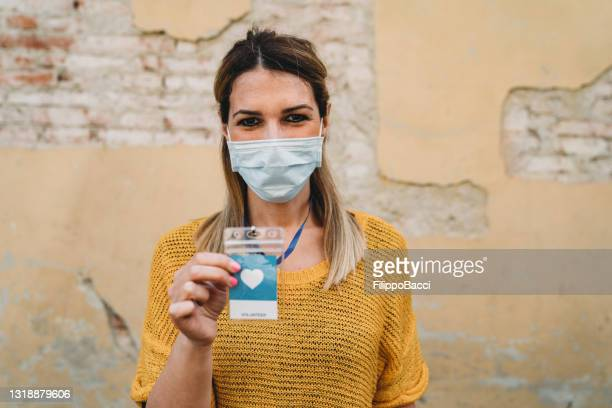portrait of a volunteer woman against an old wall - charity benefit stock pictures, royalty-free photos & images