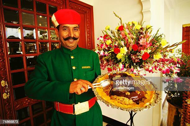 Portrait of a waiter holding a dish plate and smiling, Lake Palace, Udaipur, Rajasthan, India