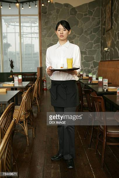 Portrait of a waitress holding a serving tray