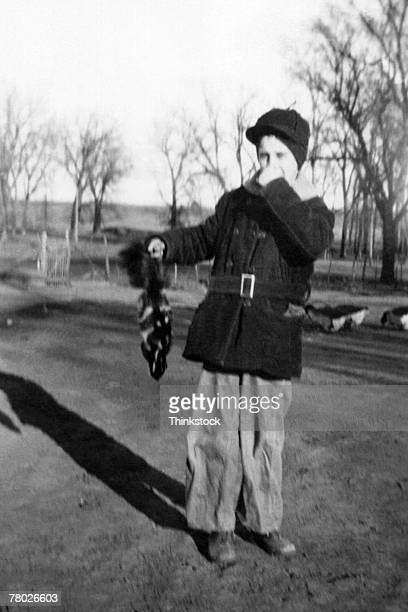 portrait of a warmly dressed boy holding his nose with one hand and a skunk in his other hand. - skunk stock photos and pictures