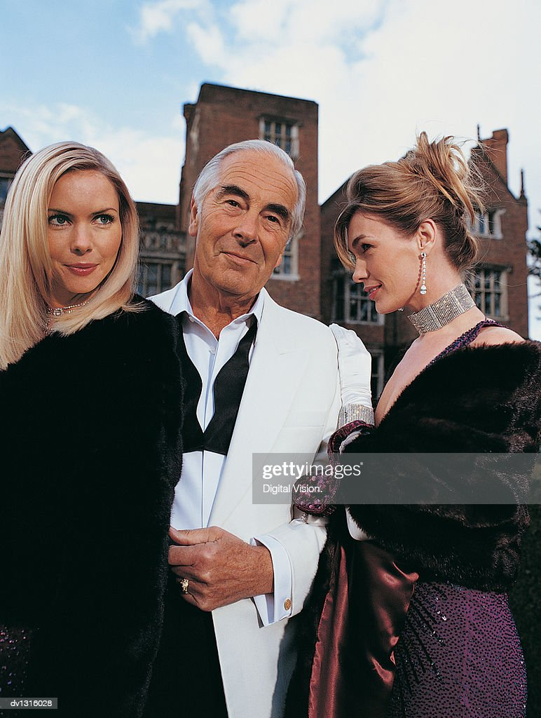 Portrait of a Wealthy Senior Man Standing Between Two Young Women : Stock Photo