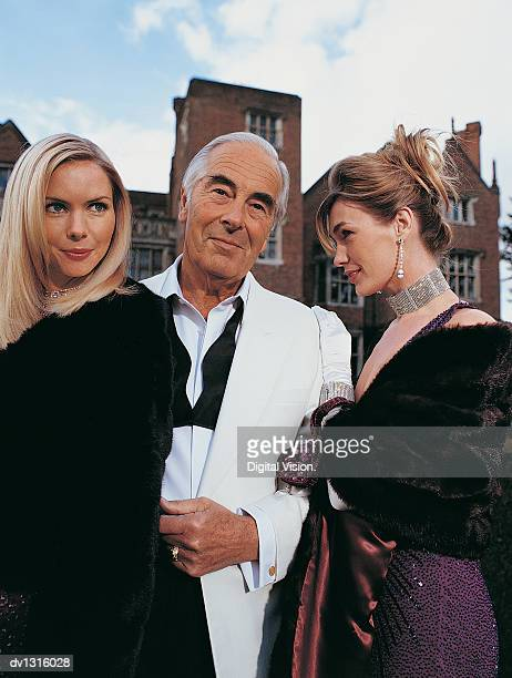 portrait of a wealthy senior man standing between two young women - may december romance stock photos and pictures