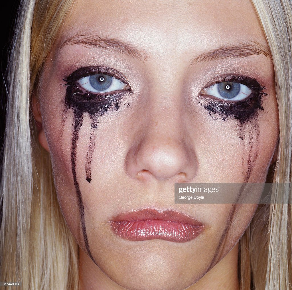 portrait of a weeping young woman with smudged kohl on her face : Stock Photo