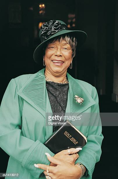 portrait of a well dressed senior woman smiling and holding a bible - free bible image stock pictures, royalty-free photos & images