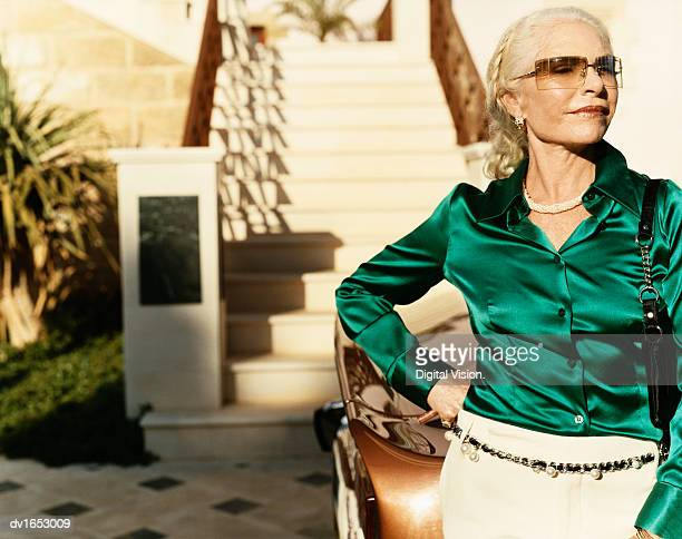 portrait of a well-dressed wealthy senior woman with attitude standing on the driveway by her car - blouse foto e immagini stock