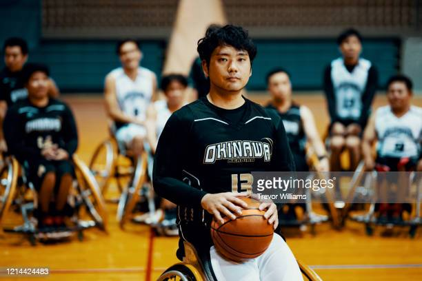 portrait of a wheelchair basketball player with his team behind him - disabilitycollection stock pictures, royalty-free photos & images