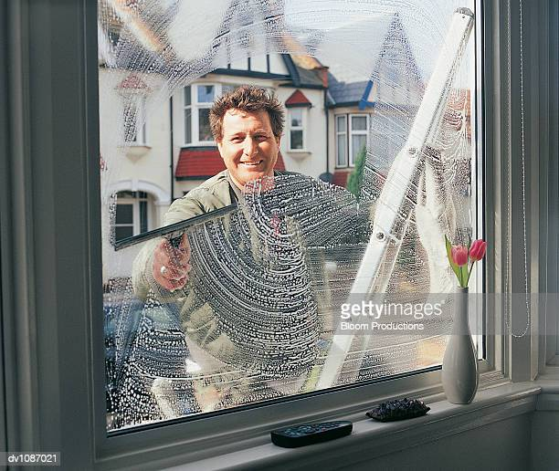 Portrait of a Window Cleaner Looking Through and Cleaning a Window