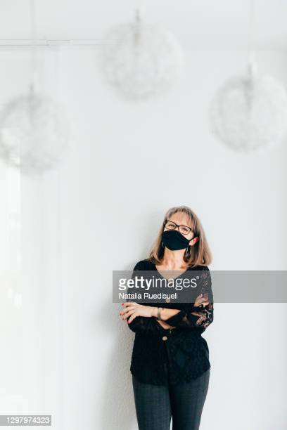 a portrait of a woman 50-55 years old wearing a black colored mask and smiling into the camera. - 55 59 years stock pictures, royalty-free photos & images