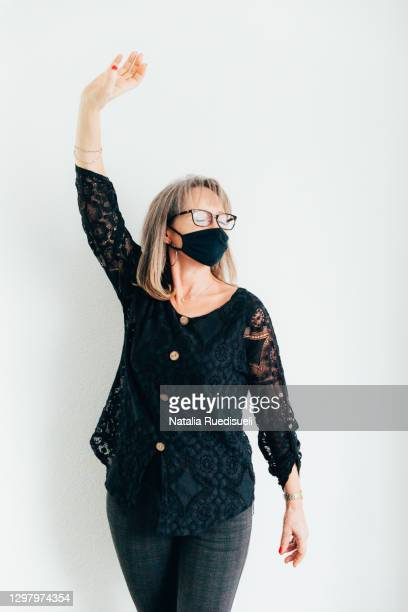a portrait of a woman 50-55 years old wearing a black colored mask , smiling and dancing with closed eyes. - 55 59 years stock pictures, royalty-free photos & images