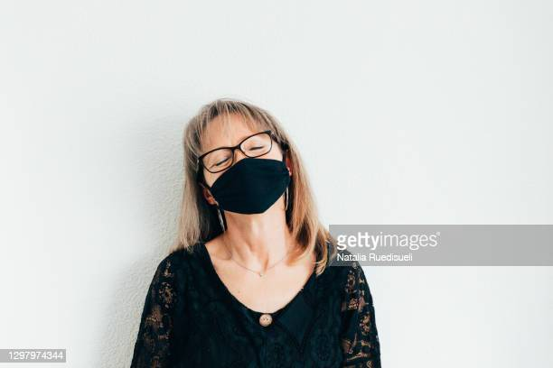a portrait of a woman 50-55 years old wearing a face protection and smiling with eyes closed. - 55 59 years stock pictures, royalty-free photos & images