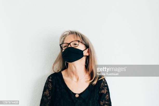 a portrait of a woman 50-55 years old wearing a face protection and smiling. - 55 59 years stock pictures, royalty-free photos & images