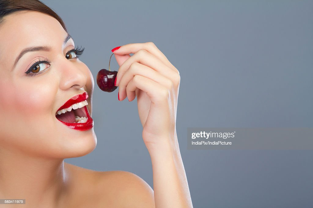 Portrait of a woman about to eat a cherry : Stock Photo