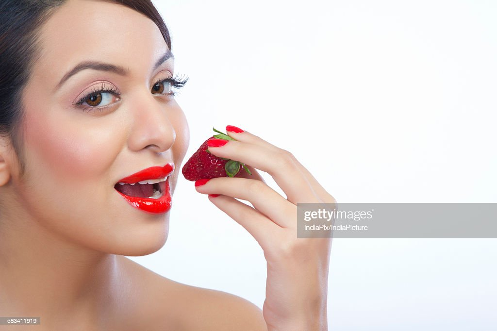 Portrait of a woman about to eat a strawberry : Stock Photo