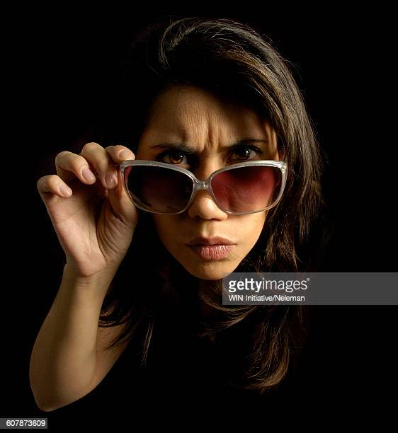 Portrait of a woman adjusting sunglasses with inquisitive expressions on her face