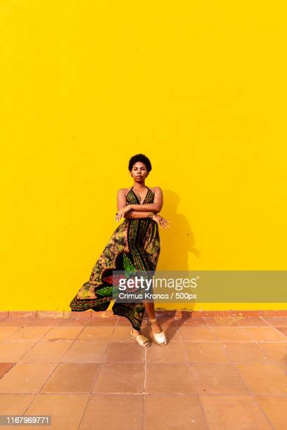 portrait of a woman against a yellow wall - yellow dress stock pictures, royalty-free photos & images