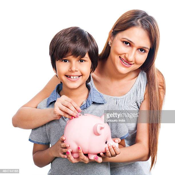 Portrait of a woman and her son putting a coin into a piggybank