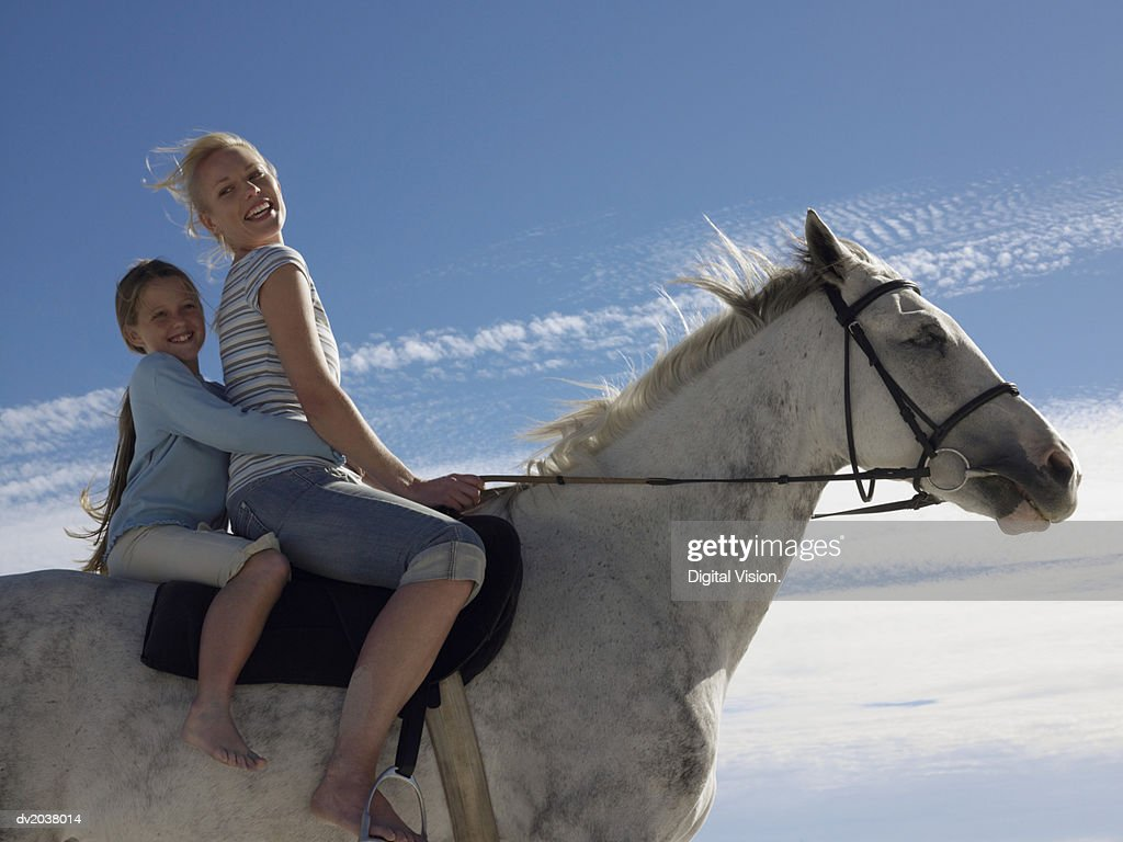 Portrait of a Woman and Her Young Daughter Sitting on a White Horse : Stock Photo