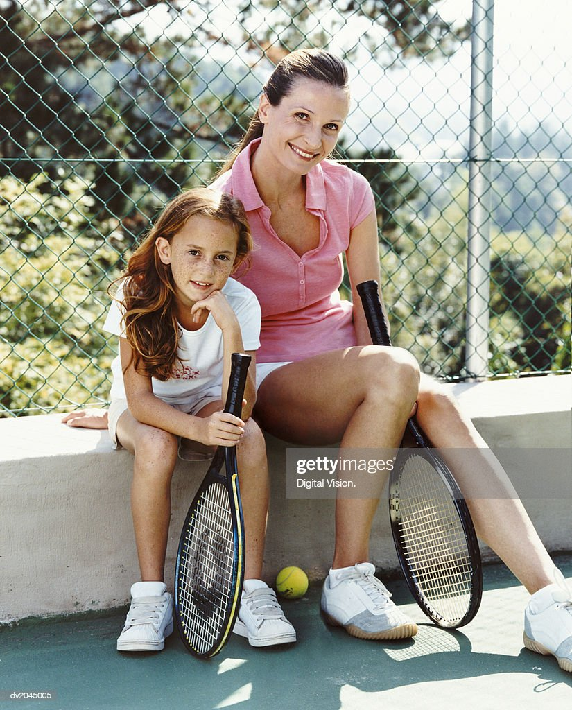 Portrait of a Woman and Her Young Daughter Sitting on the Wall of a Tennis Court, Holding Racquets : Stock Photo