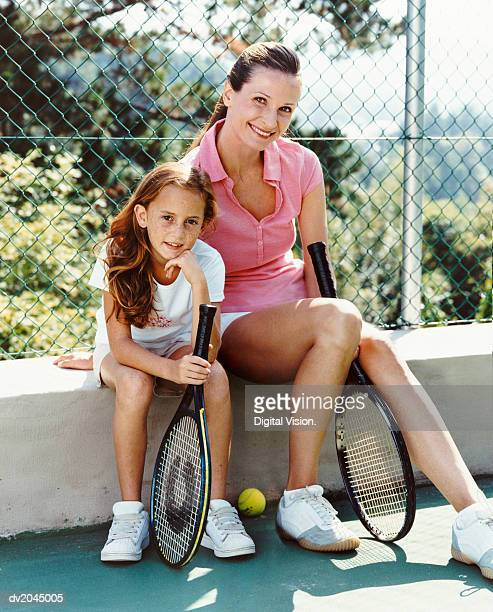 Portrait of a Woman and Her Young Daughter Sitting on the Wall of a Tennis Court, Holding Racquets
