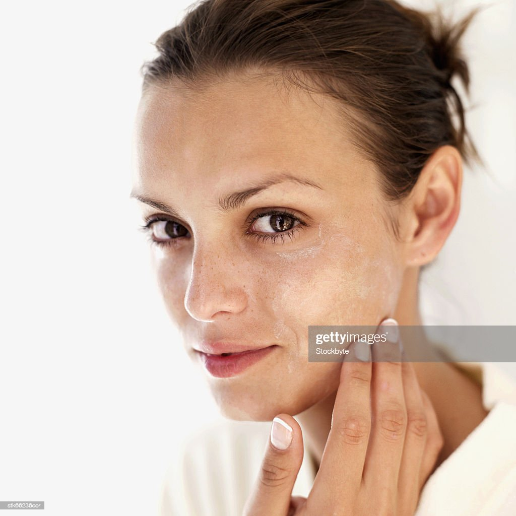 portrait of a woman applying face cream : Stock Photo
