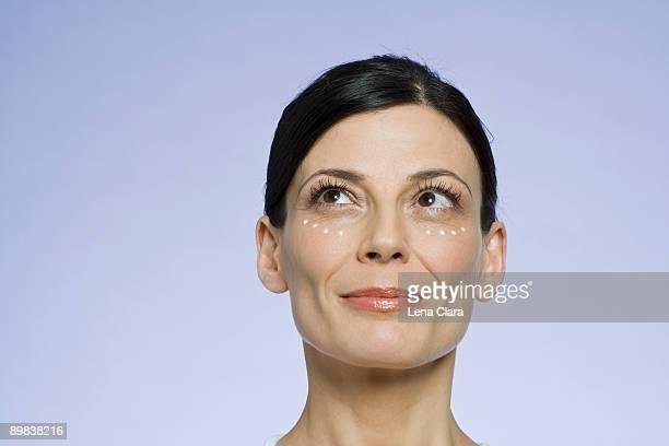 Portrait of a woman applying moisturizer