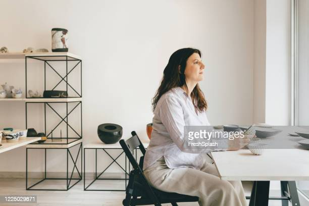 portrait of a woman artisan sitting at her atelier - art dealer stock pictures, royalty-free photos & images