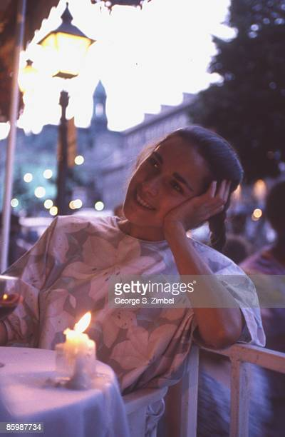 Portrait of a woman as she sits in an outdoor cafe on Place Jacques Cartier Montreal Quebec Canada 1992 The tower of the Montreal City Hall is...
