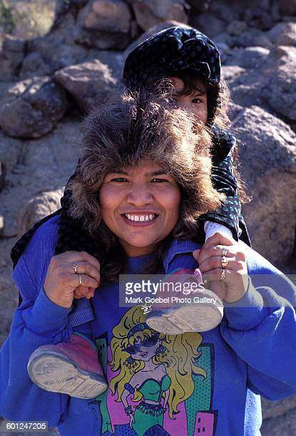 Portrait of a woman as she smiles and carries a baby on her shoulder, Juarez, Mexico, late 1980s.