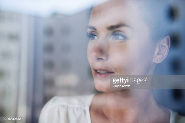 Portrait of a woman behind a window.