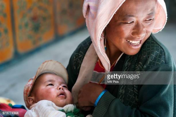 Portrait of a woman breastfeeding her son in the monastery of Tashilumpo, Shigatse, Tibet, China.