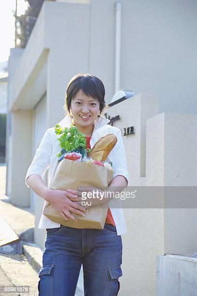 Portrait of a woman carrying groceries, portrait