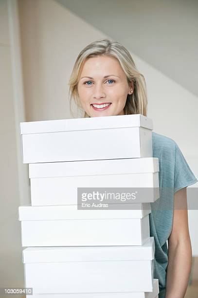 Portrait of a woman carrying shoe boxes