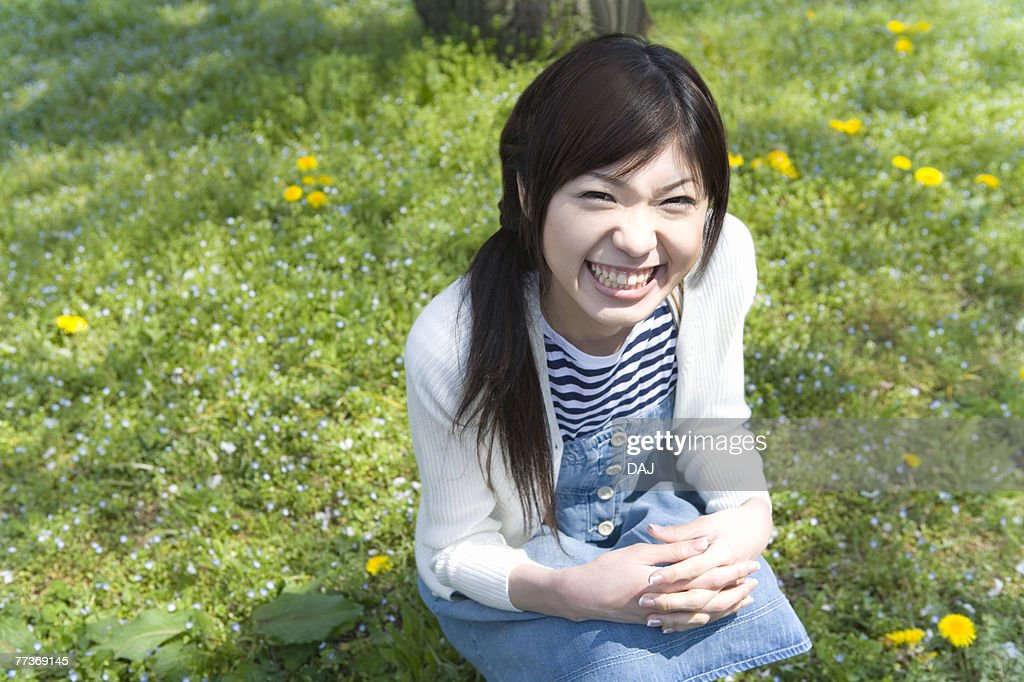 Portrait of a woman crouching down and looking at camera on field, high angle view, Japan : Photo